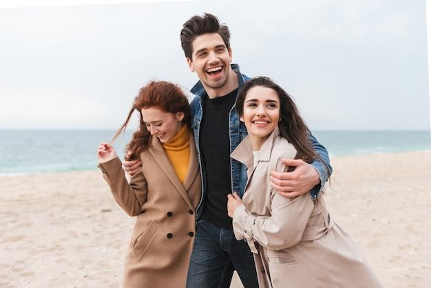 Gruppe fröhlicher junger freunde, die am meer spazieren gehen und sich umarmen