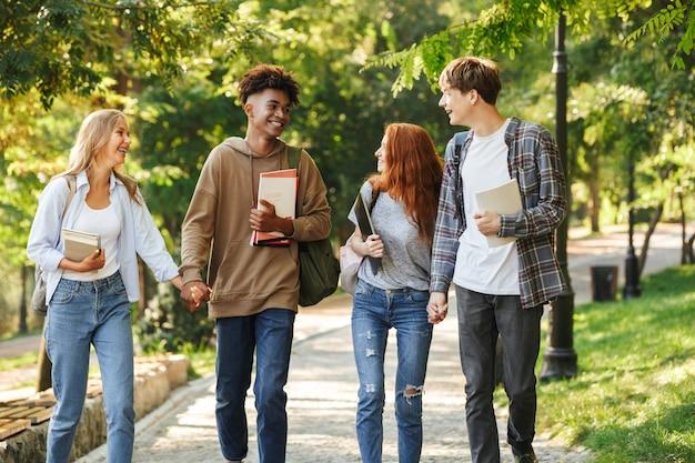 Gruppe fröhlicher studenten, die auf dem campus spazieren gehen