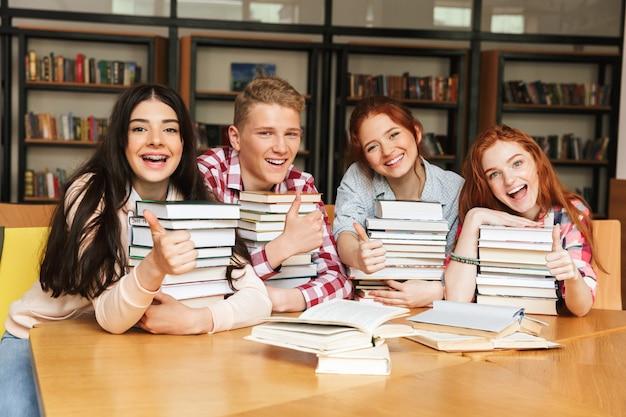 Gruppe fröhlicher teenager, die am bibliothekstisch sitzen