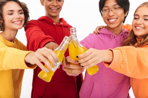 Gruppe fröhlicher teenager isoliert, mit kohlensäurehaltigen getränkeflaschen geröstet
