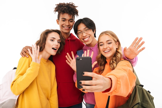 Gruppe fröhlicher teenager isoliert, rucksäcke tragend, ein selfie machend