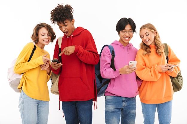 Gruppe fröhlicher teenager isoliert, rucksäcke tragend, mit handys