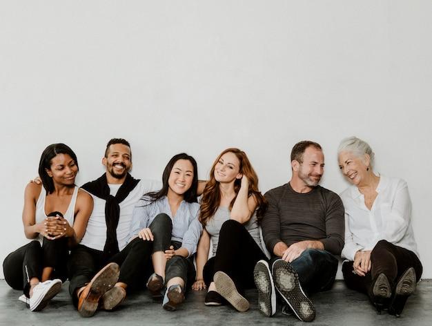 Gruppe fröhlicher, unterschiedlicher menschen, die auf einem boden in einem weißen raum sitzen