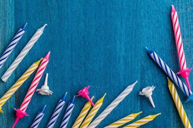 Gruppe geburtstagskerzen auf blauem hölzernem hintergrund. für geburtstagsgrußkarte.