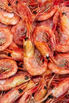 Gruppe gekochter gefrorener wilder garnelen mit kaviar, gekocht in meerwasser. hintergrund von vielen kleinen wasserkrebstieren. garnelen - ostasiatische schmankerlküche als vorspeise. flache lagenansicht der nahaufnahme von meeresfrüchten.