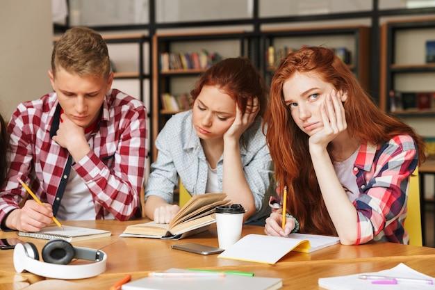 Gruppe gelangweilter teenager, die hausaufgaben machen