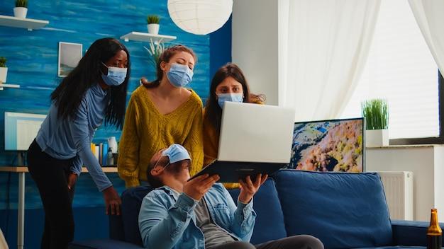Gruppe gemischter rassenfreunde, die spaß daran haben, mit gesichtsmaske soziale distanz zu halten, um die ausbreitung von coronaviren zu verhindern, indem sie videos auf dem laptop betrachten. im wohnzimmer bier trinken und pommes essen.