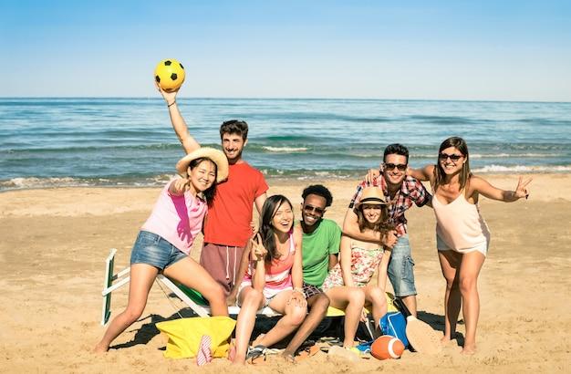 Gruppe gemischtrassige glückliche freunde, die spaß mit strandsportspielen haben