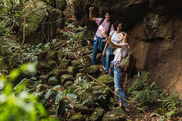 Gruppe gemischtrassiger freunde, die die natur beim wandern genießen - freunde lächeln, während sie ein selfie im dschungel machen.