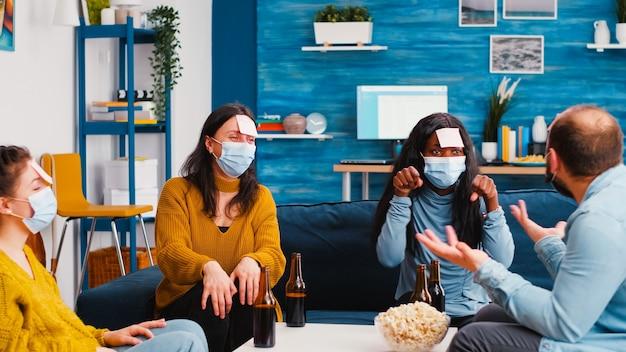 Gruppe gemischtrassiger kollegen mit schutzmasken, die ein spiel mit haftnotizen spielen