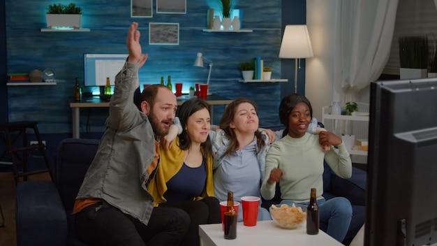 Gruppe gemischtrassiger menschen, die die fußballmannschaft jubeln, während sie spät nachts auf der couch im wohnzimmer sitzen. multiethnische freunde verbringen zeit miteinander und schauen sich fußballspiele im fernsehen an
