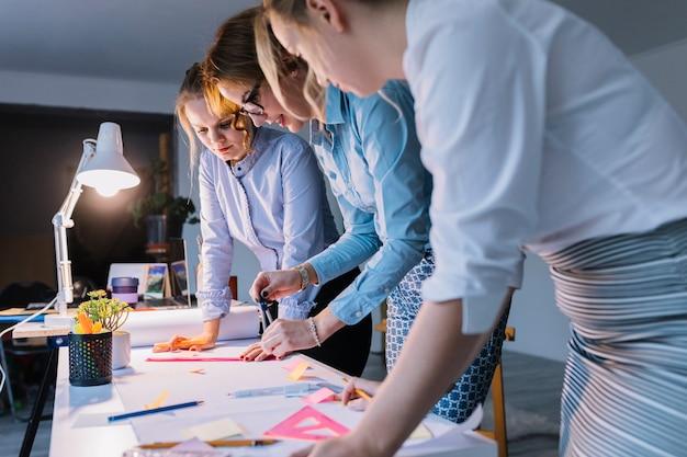 Gruppe geschäftsfrauen, die plan auf weißbuch mit instrumenten über schreibtisch am arbeitsplatz zeichnen