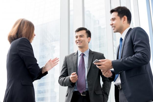 Gruppe geschäftsleute, die an der gebäudehalle im büro sprechen