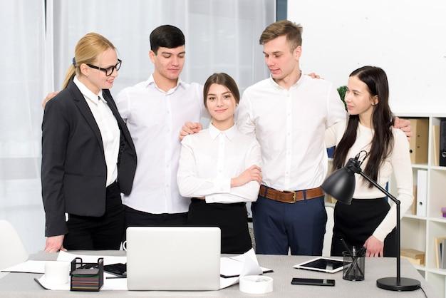 Gruppe geschäftsleute, die seinen weiblichen kollegen stehen hinter dem schreibtisch im büro betrachten