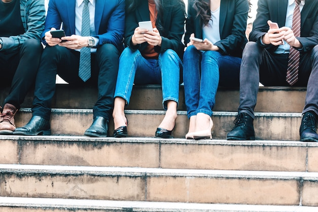 Gruppe geschäftsleute setzen technologie zusammen vom smartphone ein