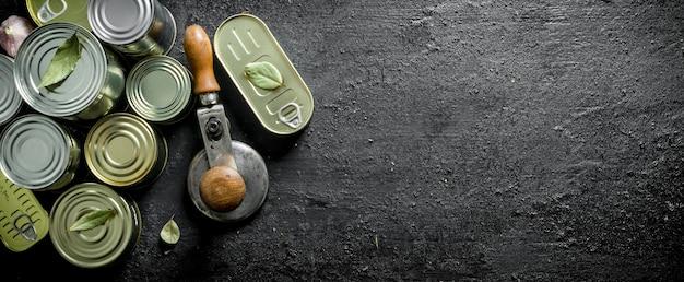 Gruppe geschlossener aluminiumdosen mit konserven. auf schwarzem rustikalem hintergrund