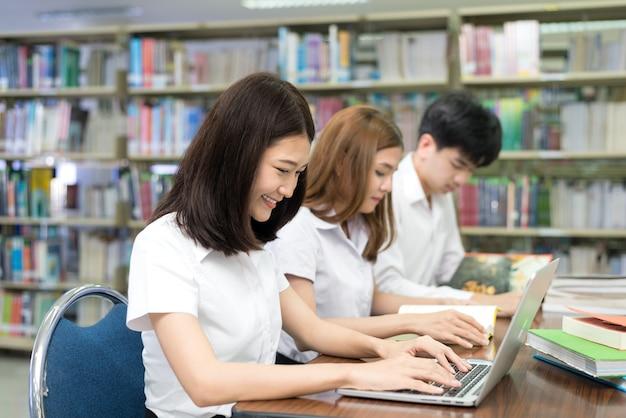 Gruppe glückliche asiatische studenten mit laptop-computer