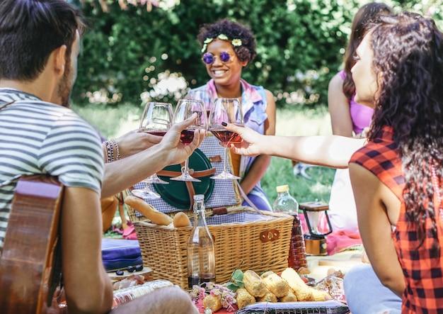 Gruppe glückliche freunde, die gläser rotwein am picknick grill im garten zujubeln