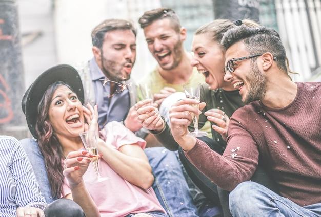 Gruppe glückliche freunde, die trinkenden champagner der partei beim werfen der konfettis im freien machen