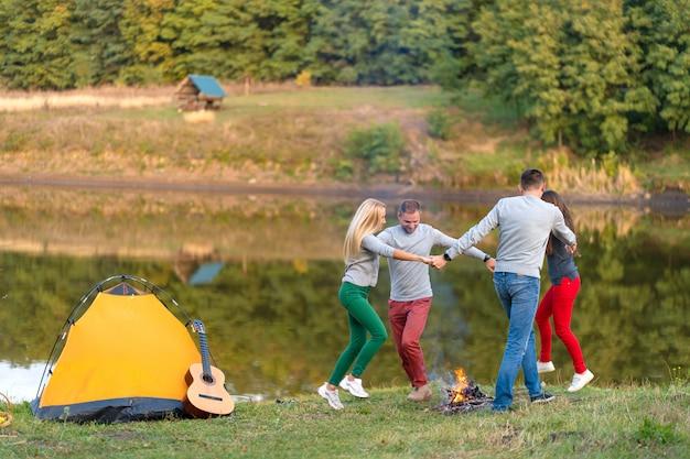 Gruppe glückliche freunde mit gitarre, spaß im freien habend, tanzen und springen nahe dem see im park