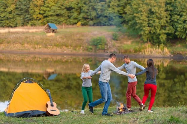 Gruppe glückliche freunde mit gitarre, spaß im freien habend, tanzen und springen nahe dem see im parkhintergrund der schöne himmel. camping spaß