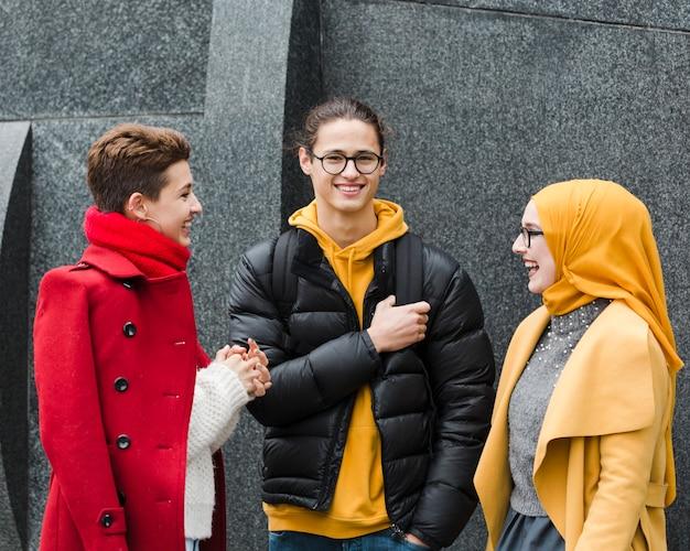 Gruppe glückliche jugendliche, die zusammen aufwerfen