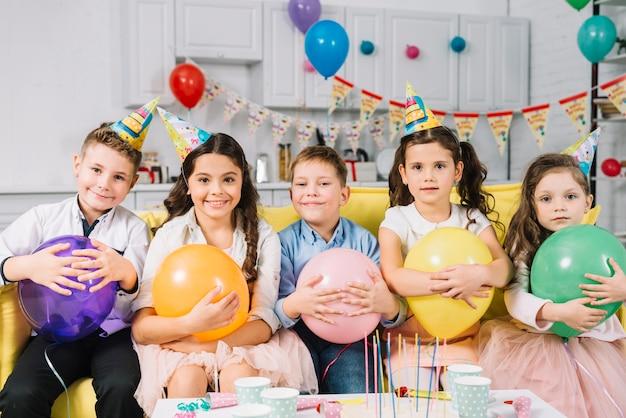Gruppe glückliche kinder mit dem ballon, der auf sofa sitzt