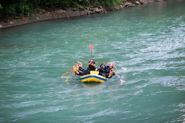 Gruppe glückliche leute mit dem führer whitewater, der auf fluss flößt und rudert.