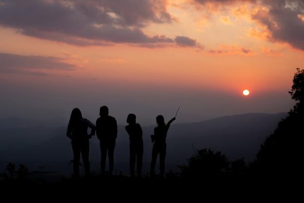 Gruppe glückliche menschen, die am sommersonnenuntergang in der natur spielen