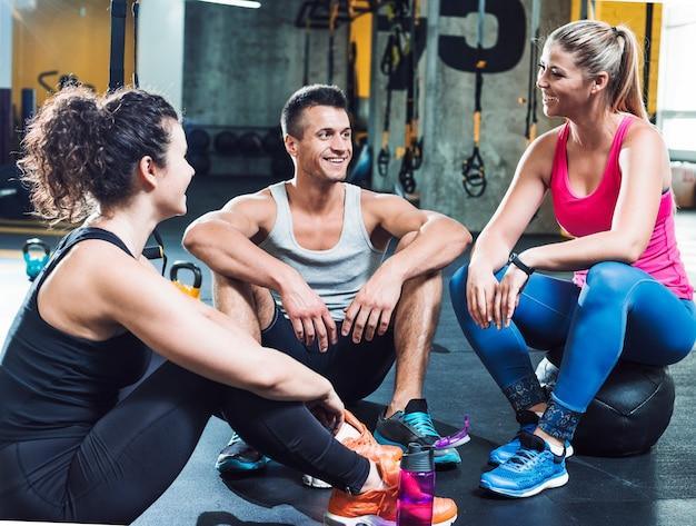 Gruppe glückliche menschen, die pause nach dem training in der turnhalle machen