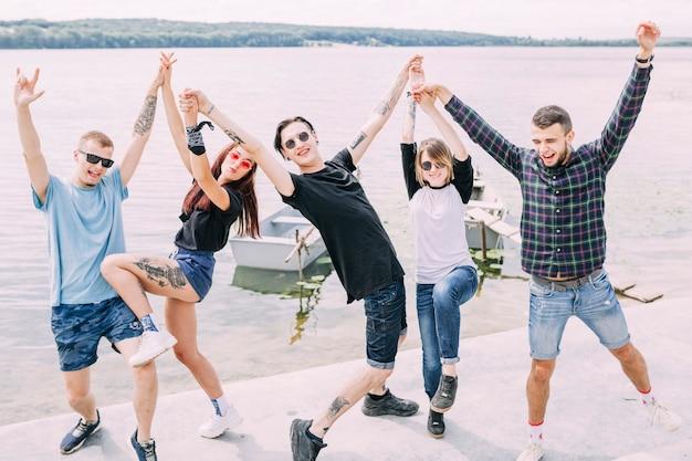 Gruppe glückliche sorglose freunde, die nahe see tanzen