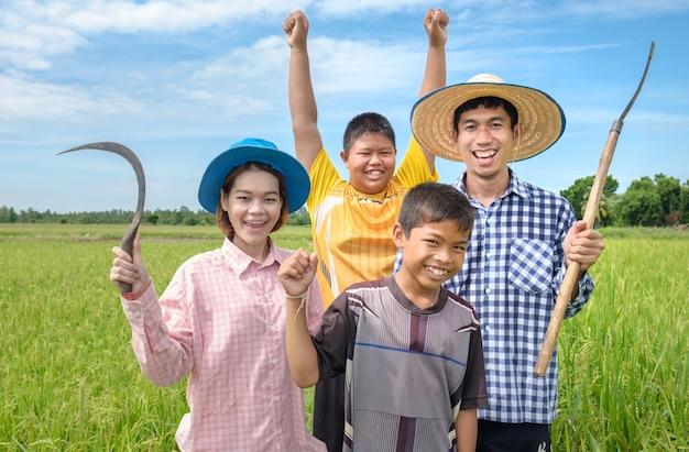 Gruppe glücklichen asiatischen landwirtmannes des lachens, frau und zwei kinder lächeln und halten werkzeuge am grünen reisfeld