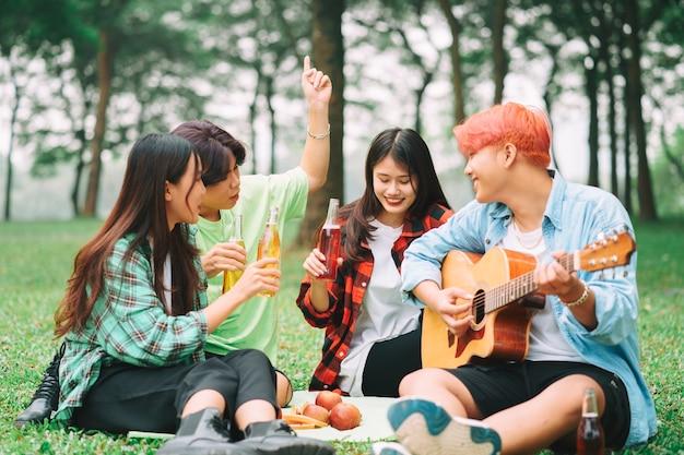 Gruppe glücklicher asiatischer junger leute, die auf der gitarre sitzen und im park singen