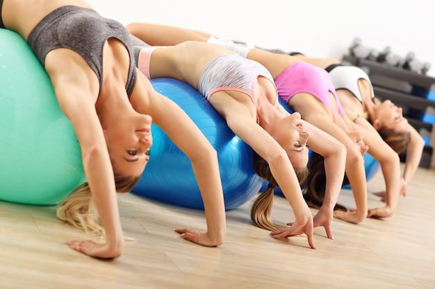 Gruppe glücklicher frauen, die aerobic mit fitten bällen machen