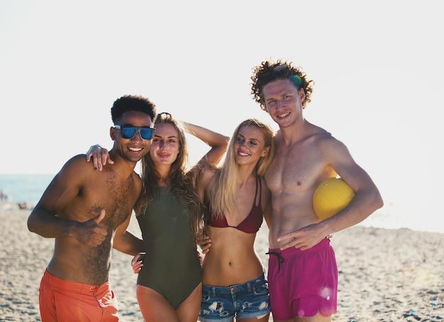 Gruppe glücklicher freunde, die am strandvolleyball am strand spielen
