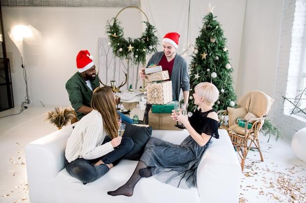 Gruppe glücklicher freunde, die auf weißem sofa sitzen und champagner halten, der weihnachtsgeschenke hält