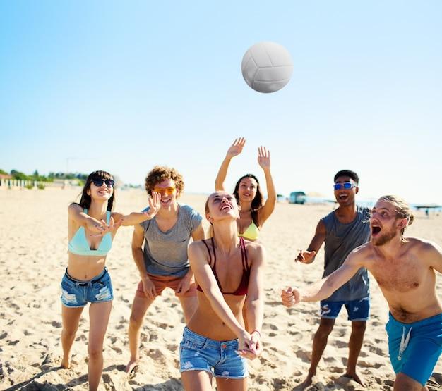 Gruppe glücklicher freunde, die beim beachvolleyball spielen