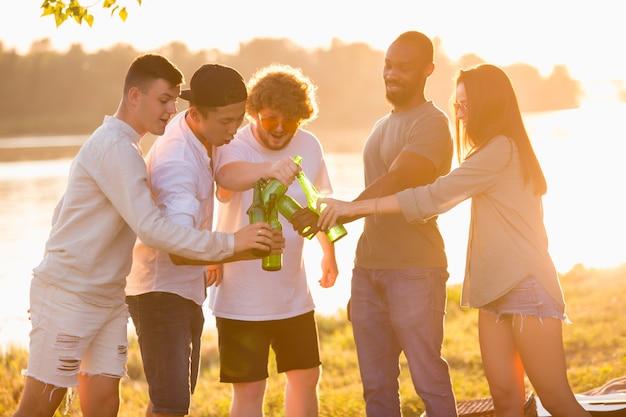 Gruppe glücklicher freunde, die beim picknick am strand bei sonnenschein bierflaschen klirren. lifestyle, freundschaft, spaß, wochenende und ruhekonzept. sieht fröhlich, fröhlich, feiernd, festlich aus.