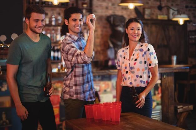Gruppe glücklicher freunde, die bier-pong-spiel spielen