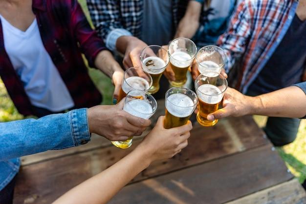 Gruppe glücklicher freunde, die gesunden lebensstil leben und sich entspannen, mit bier jubeln und bier trinken