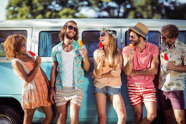 Gruppe glücklicher freunde, die mit eislutscher vor wohnmobil stehen