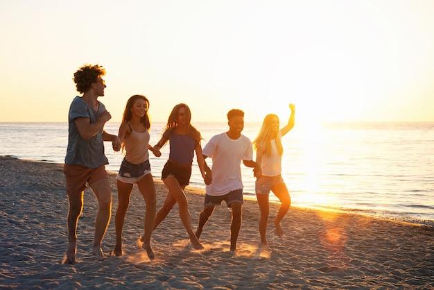 Gruppe glücklicher freunde, die sich im morgengrauen am strand des ozeans amüsieren