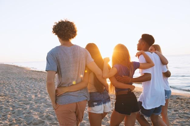 Gruppe glücklicher freunde, die spaß am ozeanstrand im morgengrauen haben