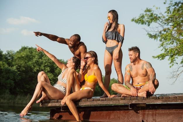 Gruppe glücklicher freunde, die spaß haben und auf dem pier am fluss lachen.