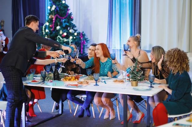 Gruppe glücklicher freunde, die weihnachten oder neujahr feiern. ein mann gießt champagner in gläser. frauen lachen, sitzen an einem tisch neben dem weihnachtsbaum.