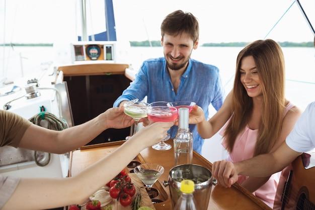 Gruppe glücklicher freunde, die wodka-cocktails in einem boot trinken