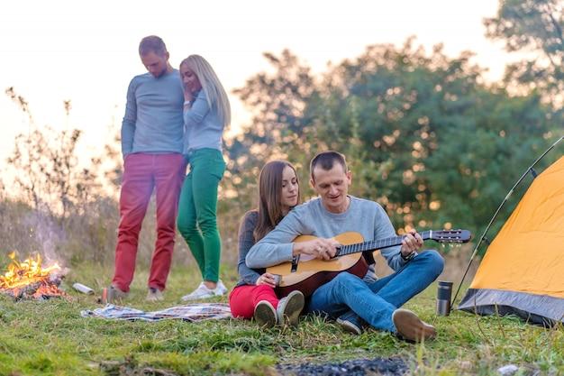 Gruppe glücklicher freunde mit gitarre, spaß im freien, in der nähe von lagerfeuer und touristenzelt. camping spaß glückliche familie