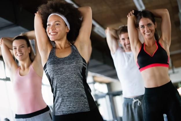 Gruppe glücklicher gemischtrassiger freunde, die zusammen im fitnessstudio trainieren