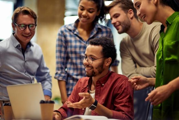 Gruppe glücklicher, gemischtrassiger geschäftsleute, die auf den laptop-bildschirm schauen und über arbeit oder projekt diskutieren