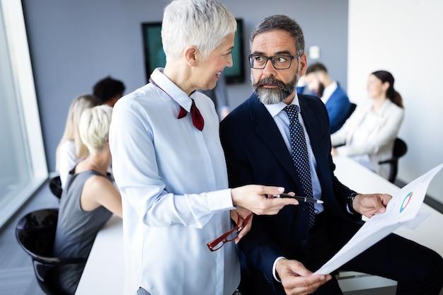 Gruppe glücklicher geschäftsleute, die in einem meeting im büro ein brainstorming durchführen